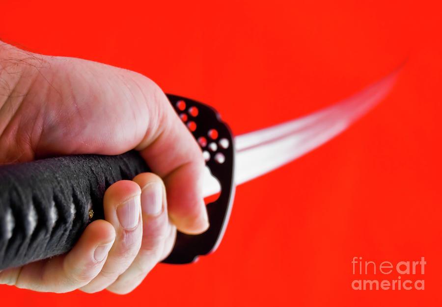 hand-holding-japanese-sword--katana-yurix-sardinelly